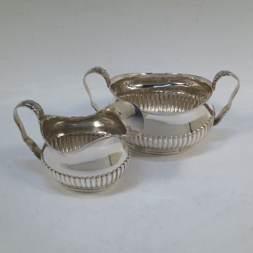 A pretty Antique Victorian Sterling Silver sugar bowl and cream jug set, having oval bellied bodies with hand-chased half-fluted decoration, applied rope-twist  borders, scroll side-handles with anthemion leaf thumb-pieces, and all sitting on collet feet. Made by Frederick Bradford Macrea of London in 1887. The dimensions of this fine hand-made antique silver sugar and creamer set are length of sugar bowl (inc. handles) 16.5 cms (6.5 inches), height 9 cms (3.5 inches), width 9.5 cms (3.75 inches), and with a total weight of approx. 310g (10 troy ounces).