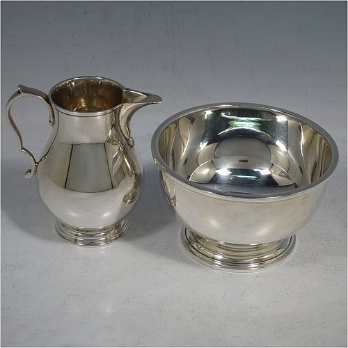 A Sterling Silver sugar and creamer set, having plain round bellied bodies, applied reeded borders, a sparrow-beak spout, and sitting on collet feet. Made by Robert Comyns of London in 1965. The dimensions of this fine hand-made silver sugar and creamer set are height of cream jug 7.5 cms (3 inches), diameter of bowl 9 cms (3.5 inches), and they weigh a total of approx. 225g (7.3 troy ounces).