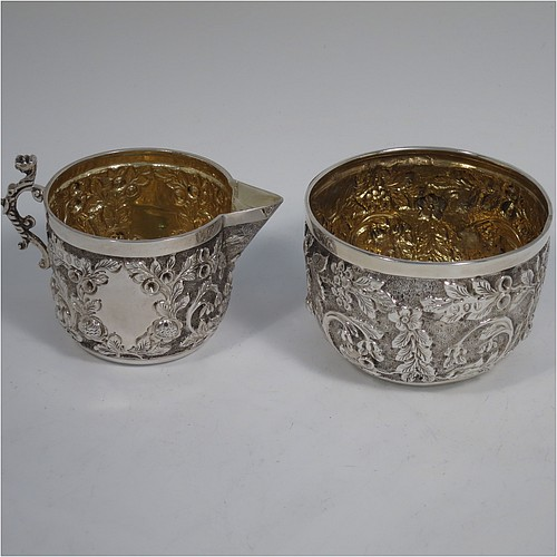 A beautiful Antique Victorian Sterling Silver sugar and creamer set, having round bodies with hand-chased floral decoration, and with gold-gilt interiors, all sitting on flat bases. Made by James Wakely & Frank Clarke Wheeler of London in 1890. The dimensions of this fine hand-made antique silver sugar and creamer set are diameter of sugar bowl 8 cms (3 inches), height of cream jug 6.5 cms (2.5 inches), and with a total weight of 133g (4.3 troy ounces).