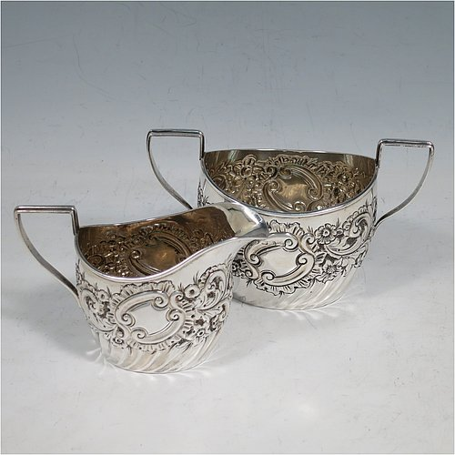 An Antique Victorian Sterling Silver sugar and cream set, having oval bellied bodies with hand-chased floral and scroll decoration above a band of swirl fluting, with applied reed borders, reeded flat-topped scroll handles, and sitting on flat bases. Made by John Wilmot of Birmingham in 1891/92. The dimensions of this fine hand-made antique silver sugar and cream set are height of sugar bowl 8 cms (6.5 inches), length of sugar bowl 13 cms (5 inches), with a total weight of approx. 145g (4.7 troy ounces).