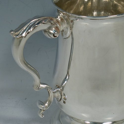 An Antique Georgian George III Sterling Silver pint tankard or mug, having a plain round bellied body, a scroll handle with an anthemion-leaf thumb-piece, and sitting on a pedestal foot. Made by John King of London in 1773. The dimensions of this fine hand-made antique silver pint mug or tankard are height 12.5 cms (5 inches), diameter at top 8 cms (3 inches), and it weighs approx. 317g (10.2 troy ounces).