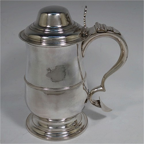 A very handsome Antique Georgian Sterling Silver lidded quart tankard, having a plain round bellied body with central reeded girdle, a hinged dome lid with hand-pierced thumb-piece, a scroll handle with heart-shaped terminal, and sitting on a pedestal foot. Made by Peter and Anne Bateman of London in 1795. The dimensions of this fine hand-made antique silver quart tankard are height 21 cms (8.25 inches), length 18 cms (7 inches), and it weighs approx. 767g (24.7 troy ounces).