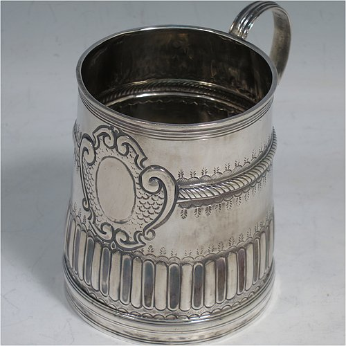 An Antique Queen Anne Sterling Silver half-pint mug / tankard, having a round straight-sided body, with reeded borders, hand-chased fluted and gadroon decoration, a scroll reeded handle, a vacant oval cartouche with scroll-work surround, and sitting on a collet foot. Made by John Cory of London in 1702. The dimensions of this fine hand-made antique silver tankard / mug are height 9 cms (3.5 inches), diameter at top 6.5 cms (2.5 inches), and it weighs approx. 116g (3.7 troy ounces).
