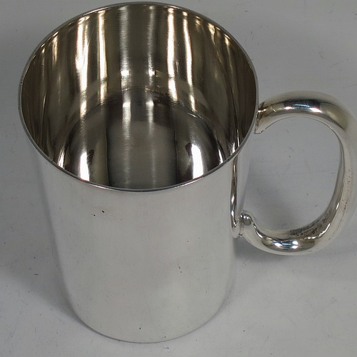 A handsome Sterling Silver half-pint mug or tankard, having a plain round body with straight tapering sides, a plain loop handle, and sitting on a flat base. Made by H. W. Plate Manufacturing Co., of Birmingham in 1929. The dimensions of this fine hand-made silver half-pint tankard or mug are height 9.5 cms (3.75 inches), diameter at top 7.5 cms (3 inches), and it weighs approx. 187g (6 troy ounces).