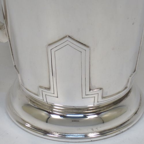 A very stylish and handsome Art Deco Sterling Silver pint mug or tankard, having a plain round body with straight tapering sides, a plain square cross-section side handle, and sitting on a pedestal foot with four applied art deco decals above. Made by Walker and Hall of Sheffield in 1941. The dimensions of this fine hand-made art deco silver pint tankard or mug are height 13 cms (5 inches), diameter at top 9 cms (3.5 inches), and it weighs approx. 316g (10.2 troy ounces).