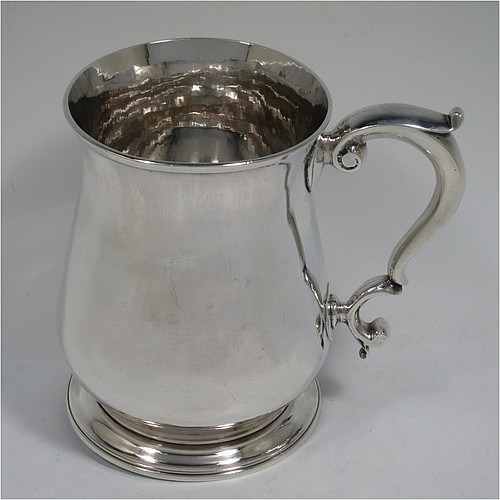 A very handsome and heavy Antique Georgian George II Sterling Silver pint tankard or mug, having a plain round bellied body, a scroll handle, and sitting on a collet foot. Made by Henry Brind of London in 1749. The dimensions of this fine hand-made antique silver pint mug or tankard are height 12.5 cms (5 inches), diameter at top 9 cms (3.5 inches), and it weighs approx. 377g (12.2 troy ounces).