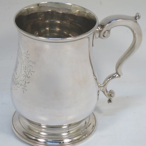 A very handsome Antique Georgian George II Sterling Silver pint tankard, having a plain round bellied body, a scroll handle with thumb-piece, and sitting on a pedestal foot. Made by William Cripps of London in 1755. The dimensions of this fine hand-made antique silver pint mug or tankard are height 11.5 cms (4.5 inches), diameter at top 8 cms (3 inches), and it weighs approx. 362g (11.7 troy ounces). Please note that this item is crested.