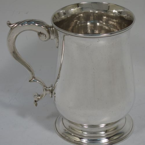 A very handsome Antique Georgian Sterling Silver pint tankard, having a plain round bellied body, a scroll handle with anthemion leaf thumb-piece, and sitting on a collet foot. Made by James Jennings of London in 1773. The dimensions of this fine hand-made antique silver pint mug or tankard are height 12 cms (4.75 inches), diameter at top 8 cms (3 inches), and it weighs approx. 298g (9.6 troy ounces).