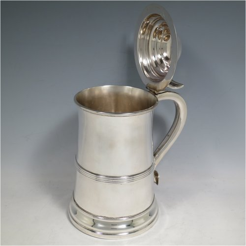 An Antique late Victorian Sterling Silver lidded quart tankard in a George I style, having a plain straight-sided body with an applied reeded band, a hinged dome lid with pierced thumb-piece, a scroll handle, and sitting on a reeded collet foot. Made by Elkington & Co., of Birmingham in 1900. The dimensions of this fine hand-made antique silver tankard are height 21.5 cms (8.5 inches), length 15 cms (6 inches), and it weighs approx. 682g (22 troy ounces).