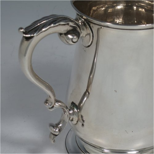 An Antique Georgian Sterling Silver pint tankard, having a plain round baluster body, a scroll handle, and sitting on a collet foot. Made by Fuller White of London in 1763. The dimensions of this fine hand-made antique silver tankard are height 12 cms (4.75 inches), diameter at top 8 cms (3 inches), and it weighs approx. 340g (11 troy ounces).
