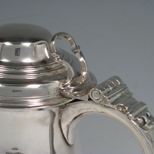 Antique Georgian sterling silver lidded quart tankard, having a plain bellied body, a hinged dome lid with thumb-piece, a scroll handle, sitting on a pedestal foot. Made by William Cripps of London in 1760. Weight approx. 758g (24.5 troy ounces). Please note that this piece has a small part-crest on the front of the body.