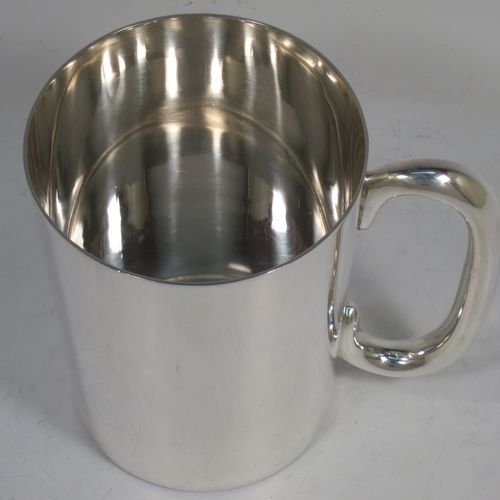 A very handsome and heavy Sterling Silver pint mug or tankard, having a plain round body with straight tapering sides, a plain loop handle, and all sitting on a flat base. Made by the Barker Brothers of Birmingham in 1932. The dimensions of this fine hand-made sterling silver pint tankard or mug are height 11.5 cms (4.5 inches), diameter at top 9 cms (3.5 inches), and it weighs approx. 404g (13 troy ounces).