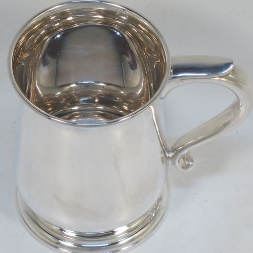 A very handsome Sterling Silver half-pint tankard or mug, having a plain round body with tucked under belly, a scroll handle with plain thumb-piece, and sitting on a pedestal foot. Made by Mappin and Webb of Sheffield in 1976. The dimensions of this fine hand-made silver half-pint mug or tankard are height 10 cms (4 inches), diameter at top 7 cms (2.75 inches), and it weighs approx. 191g (6.2 troy ounces).