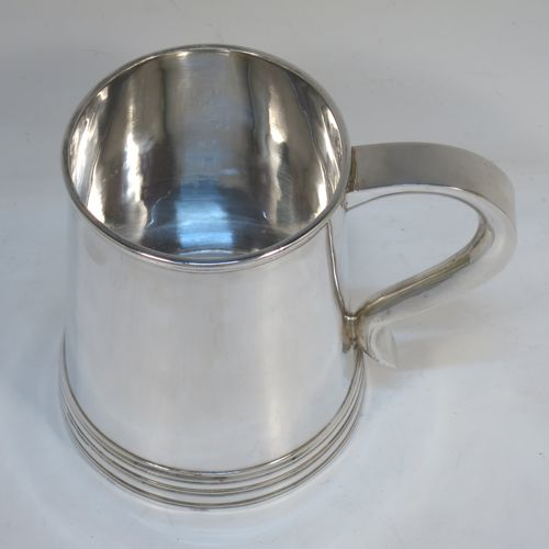 A very handsome George I style Sterling Silver pint tankard, having a plain round straight-sided body with hand-chased reeded borders, a plain scroll handle, and sitting on a collet foot. Made by Goldsmiths and Silversmiths  of London in 1921. The dimensions of this fine hand-made silver tankard are height 12 cms (4.75 inches), diameter at top 8.5 cms (3.3 inches), and it weighs approx. 374g (12 troy ounces).