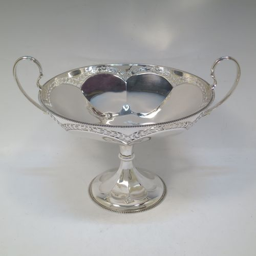 A very pretty Sterling Silver tazza dish, having a round body with an applied gadroon border above a lobed band of hand-pierced floral decoration, with two scroll side-handles, and all sitting on a matching pedestal foot. Made by Elkington and Co., of Birmingham in 1920. The dimensions of this fine hand-made silver tazza dish are height 18.5 cms (7.3 inches), diameter 21 cms (8.25 inches), and it weighs approx. 615g (19.8 troy ounces).