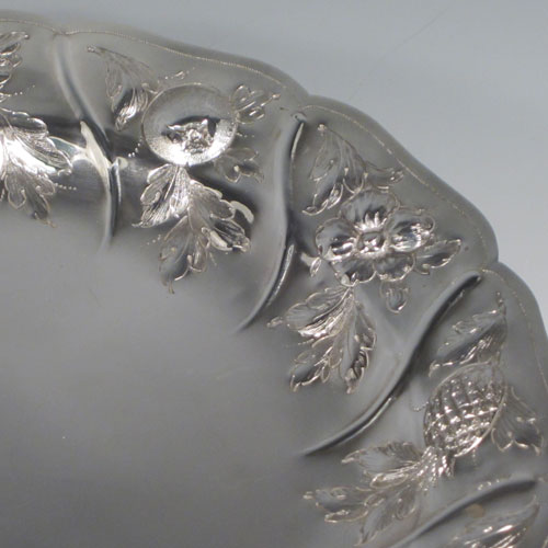 Antique Victorian sterling silver tazza dish, having a round body with hand-chased floral and fruit decoration, sitting on a pedestal foot with matching decoration and swirl fluting. Made by Henry Holland of London in 1874. The dimensions of this fine hand-made silver tazza dish are height 21 cms (8.25 inches), diameter 26 cms (10.25 inches), and it weighs approx. 838g (27 troy ounces).
