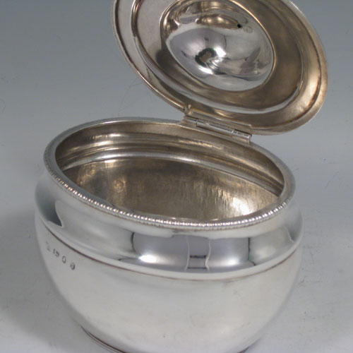 An Antique Georgian Sterling Silver tea caddy box, having a plain oval bellied body with a hand-chased reeded upper band and gadroon border, a hinged domed lid with a cast ball finial, and all sitting on a flat base. Made by John Watson of Sheffield in 1813. The dimensions of this fine hand-made antique silver tea caddy box are height 12 cms (4.75 inches), length 11.5 cms (4.5 inches), width 9 cms (3.5 inches), and it weighs approx. 217g (7 troy ounces).