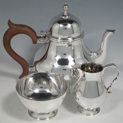 Sterling silver three-piece tea set, ccnsisting of teapot, sugar bowl, and cream jug, in a George I style having plain round baluster bodies, a hinged and domed lid, wooden insulated handle, a sparrow-beak style cream jug, and all sitting on pedestal feet. Made by Wakely and Wheeler of London in 1972. The dimensions of this fine hand-made silver tea set are height of teapot 16.5 cms (6.5 inches), length 21 cms (8.25 inches), and it weighs a total of approx. 830g (26.7 troy ounces).