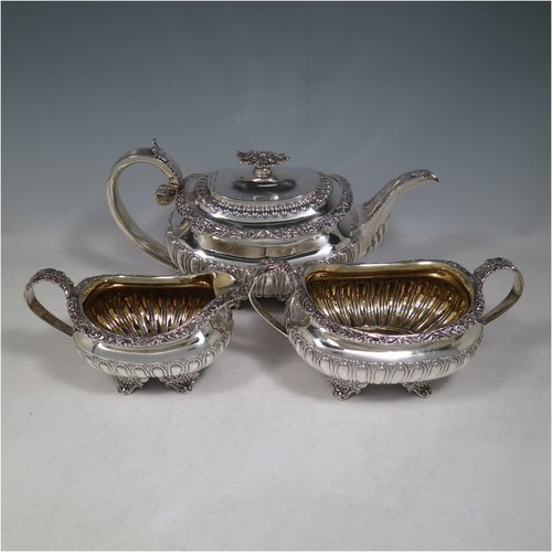 An Antique Georgian Sterling Silver three-piece Regency style tea set, having a teapot, sugar bowl and cream jug. The bodies all hand-chased with half-fluted decoration, the sugar and creamer with gold-gilt interiors, the teapot with silver handle and finial, and an invisibly hinged lid, all with applied cast acanthus leaf and floral borders, and all sitting on four floral cast flange feet. Made by Joseph Angell of London in 1824. The dimensions of this fine hand-made antique silver tea service are length of teapot 30.5 cms (12 inches), height 16 cms (6.3 inches), and it weighs a total of approx. 1,395g (45 troy ounces).