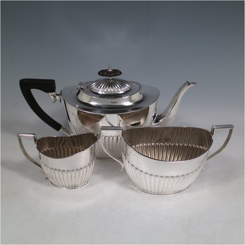 An Antique Victorian Sterling Silver three-piece tea set in a Queen Anne style, having oval shaped bodies, fine half-fluted hand-chased decoration, reeded handles on the sugar & cream jug, and a wooden handle & finial on the teapot, and all sitting on flat bases. Made by the Barker Brothers of Birmingham in 1900. The dimensions of this fine hand-made antique silver tea set are length of teapot 29 cms (11.5 inches), height 16 cms (6.25 inches), and the total weight is approx. 810g (26 troy ounces).