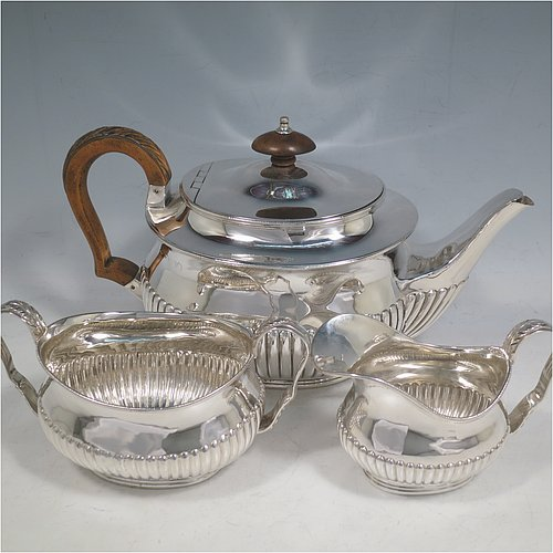 An Antique Victorian Sterling Silver three-piece tea set in a Queen Anne style, having oval shaped bodies, fine half-fluted hand-chased decoration, with anthemion leaf handles on the sugar & cream jug, and a wooden handle & finial on the teapot, with the latter having a flat invisible hinge, and all sitting on collet foot bases. Made by Frederick Bradford Macrea of London in 1887. The dimensions of this fine hand-made antique silver tea set are length of teapot 27 cms (10.5 inches), height 15 cms (6 inches), and the total weight is approx. 900g (29 troy ounces).