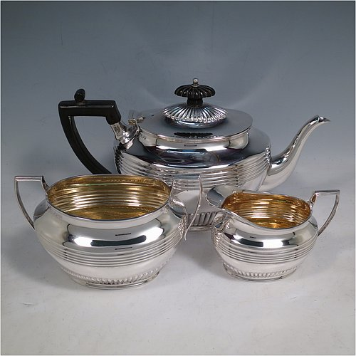 An Antique Victorian Sterling Silver three-piece tea set, having oval shaped bodies, with fine half-fluted and reeded hand-chased decoration, reeded handles on the sugar & cream jug together with gold-gilt interiors, and a wooden handle & finial on the teapot, and all sitting on collet foot bases. Made by Henry Stratford of Sheffield in 1900. The dimensions of this fine hand-made antique silver tea set are length of teapot 28 cms (11 inches), height 15 cms (6 inches), and the total weight is approx. 775g (25 troy ounces).
