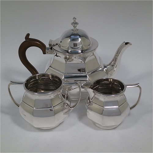 An Antique Sterling Silver three-piece bachelor tea set, having hexagonal panelled bodies, the teapot with a domed hinged lid with a cast finial, a brown wooden scroll handle, and the cream and sugar bowl with loop handles, all sitting on collet feet. Made by Nathan and Hayes of Birmingham in 1915. The dimensions of this fine hand-made antique silver tea set are height of teapot 15 cms (6 inches), length of teapot 20 cms (8 inches), with a total weight of approx. 648g (21 troy ounces).