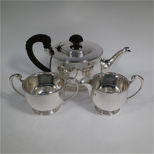 A Sterling Silver Art Deco three-piece tea set, consisting of a teapot, sugar bowl, and cream jug, in a plain round bellied style, with applied reeded borders, the sugar bowl and cream jug with cast scroll handles, the teapot with a hinged stepped lid, wooden finial, and a wooden insulated handle, and all sitting on stepped collet feet. Made by William Neale Limited of Birmingham in 1937. The dimensions of this fine hand-made Art Deco silver tea set are height of teapot 13 cms (5 inches), length 25.5 cms (10 inches), and it weighs a total of approx. 786g (24 troy ounces).