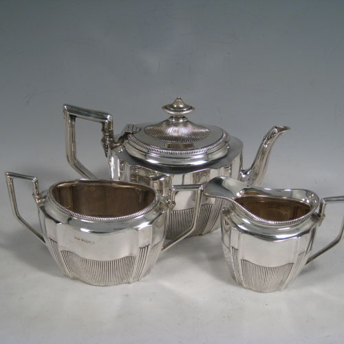 Antique Victorian sterling silver Bachelor three-piece tea set, having oval shaped bodies, fine half-fluted hand-chased decoration, gadroon borders, and an insulated silver handle on the teapot. Made by William Aitken of Chester in 1894. The dimensions of this fine hand-made silver tea set are length of teapot 19 cms (7.5 inches), height 11.5 cms (4.5 inches), and the total weight is approx. 416g (13.5 troy ounces).