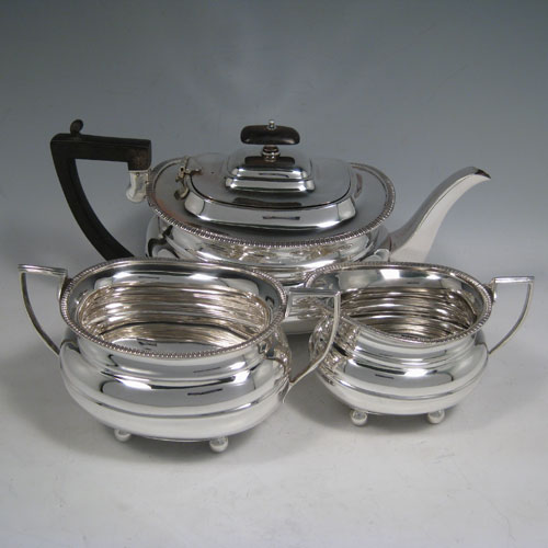 Sterling silver three-piece tea and coffee set, having plain baluster bodies, applied gadroon borders, the teapot with hinged lid, wooden finial and handle, and all sitting on four ball feet. Made by William Hutton of Sheffield in 1918. The dimensions of this fine hand-made tea service are length of teapot 29 cms (11.5 inches), height 15 cms (6 inches), and the total weight is approx. 1,147g (37 troy ounces).