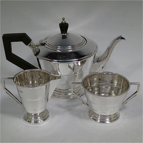 A very handsome Sterling Silver Art Deco three-piece tea set, consisting of a teapot, sugar bowl, and cream jug, in a plain round stepped style with hand-chased reeded decoration and angular handles, the teapot with a black wooden handle, finial, and a hinged lid, and all sitting on round stepped pedestal feet. Made by Joseph Gloster Ltd., of Birmingham in 1938. The dimensions of this fine hand-made Art Deco silver tea set are height of teapot 15 cms (6 inches), length 24 cms (9.5 inches), and it weighs a total of approx. 560g (18 troy ounces).