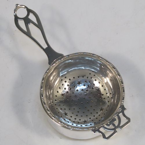 A pretty Sterling Silver tea strainer and bowl, having a hand-pierced handle, a round hand-pierced bowl with hand-cut side holder and an applied pearl and bead border, and sitting on a plain round dregs stand with straight sides. Made by Walker and Hall of Birmingham in 1928. The dimensions of this fine hand-made silver tea strainer & stand are length 12 cms (4.75 inches), diameter of stand 6 cms (2.25 inches), with a total weight of approx. 54g (1.7 troy ounces).
