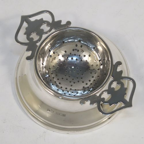 A handsome Sterling Silver tea strainer and dregs bowl in a Georgian lemon strainer style, having a round hand-pierced bowl, with two hand-pierced side-handles, and sitting on an original plain round pedestal style dregs stand. Made by Lanson Ltd. of Birmingham in 1960. The dimensions of this fine hand-made silver tea strainer and bowl are height 3 cms (1.25 inches), width across handles 10 cms (4 inches), and it weighs a total of approx. 65g (2 troy ounces)