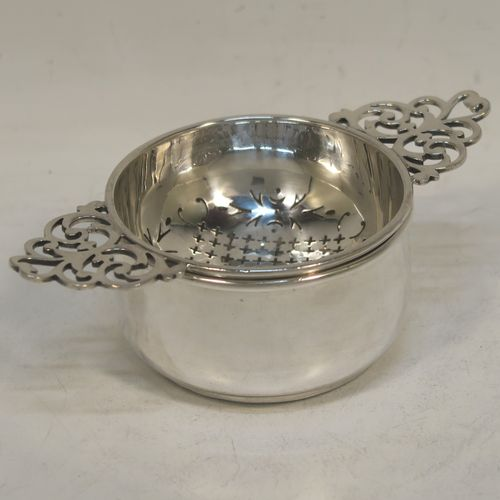 A handsome Sterling Silver tea strainer and dregs bowl in a Georgian lemon strainer style, having a round hand-pierced bowl, with two hand-pierced side-handles, and sitting on an original plain round dregs stand with a flat base. Made by Mappin and Webb of Birmingham in 1930. The dimensions of this fine hand-made silver tea strainer and bowl are height 4 cms (1.5 inches), width across handles 12 cms (4.75 inches), and it weighs a total of approx. 86g (2.8 troy ounces).