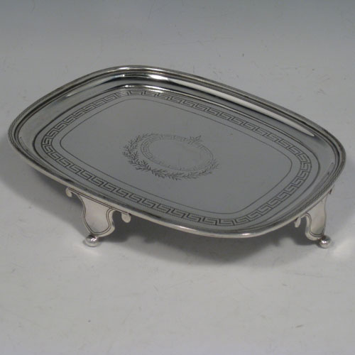 Antique Georgian sterling silver teapot stand with hand-engraved Greek-key decoration, central vacant cartouche with laurel leaf work, reeded border, and sitting on four cut flanged feet. Made by Andrew Fogelberg of London in 1806. Length 15 cms (6 inches), width 12 cms (4.75 inches), height 2.5 cms (1 inch). Weight approx. 5 troy ounces (155g).
