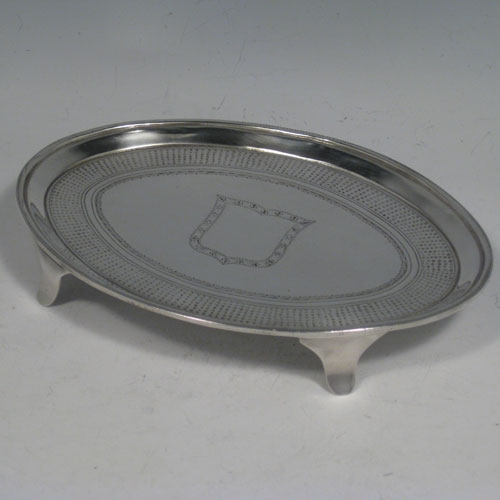 Antique Georgian sterling silver oval tea pot stand pin-chasing decoration, central cartouche, and sitting on four plain flange feet. Made by John Hutson of London in 1792. Length 16.5 cms (6.5 inches), width 12.5 cms (5 inches). Weight approx. 135g (4.4 troy ounces).