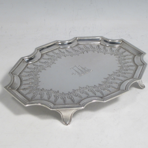 Antique Georgian sterling silver Neoclassical style teapot stand having a shaped rectangular body with a raised border, a hand-engraved ground with floral decoration, and sitting on four flange feet. Made by Henry Chawner of London in 1789. The dimensions of this fine hand-made silver teapot stand are length 16.5 cms (6.5 inches), width 12.5 cms (5 inches), and it weighs approx. 140g (4.5 troy ounces). Please note that this item is crested.