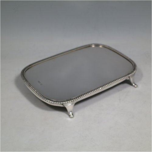An Antique Georgian sterling silver teapot stand having a rectangular body with rounded corners, an applied gadroon border, a plain ground with wooden base, and sitting on four flange feet. Made in ca. 1810. The dimensions of this fine hand-made silver teapot stand are length 18 cms (7 inches), and width 12.5 cms (5 inches). Please note that this item only has a makers mark, a duty mark, and a sterling standard mark.