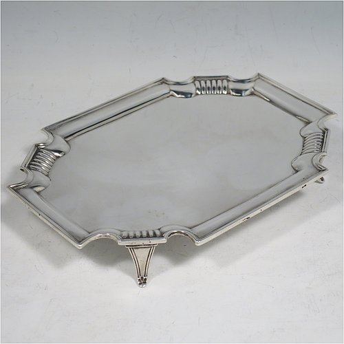An Antique Edwardian Scottish Sterling Silver teapot stand, having a shaped rectangular body with a plain ground, with hand-chased fluted cut corners and an applied reeded border, all sitting on four flange feet. Made by Hamilton & Inches of Edinburgh in 1903. The dimensions of this fine hand-made antique silver teapot stand are length 17 cms (6.75 inches), width 12.5 cms (5 inches), and it weighs approx. 155g (5 troy ounces).