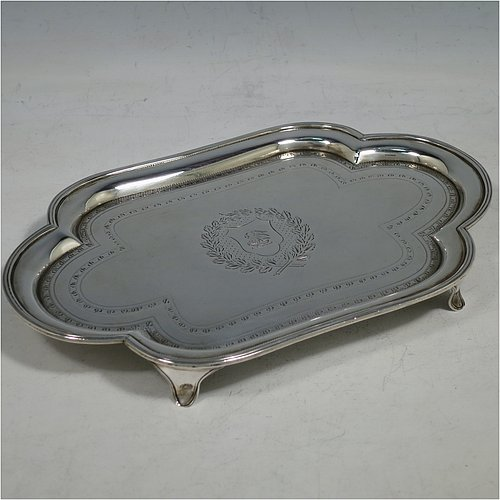 An Antique Georgian Sterling Silver Neoclassical style teapot stand having a lobed rectangular body with a raised edge and applied reeded border, a hand-engraved ground with floral bands of decoration and a central cartouche with laurel-leaf surround, and all sitting on four flange feet. Made by Henry Chawner of London in 1792. The dimensions of this fine hand-made antique silver teapot stand are length 20 cms (8 inches), width 13 cms (5.25 inches), and it weighs approx. 191g (6 troy ounces). Please note that this item is crested.