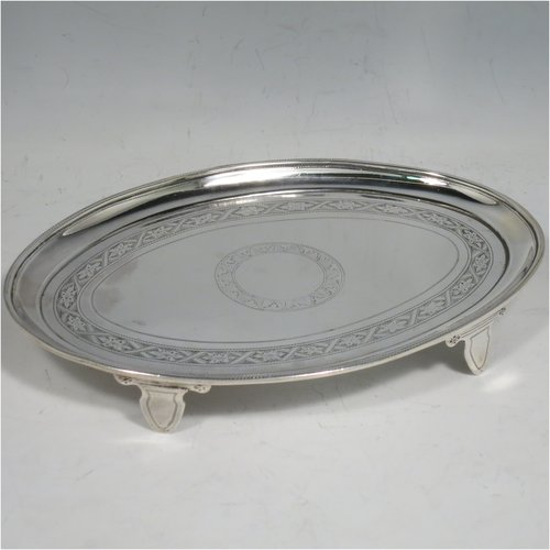An Antique Victorian Sterling Silver teapot stand, having an oval body with a band of hand-engraved floral decoration, a raised border with a rope-twist edge, and sitting on four flange feet. Made in Birmingham in 1896. The dimensions of this fine hand-made silver teapot stand are length 17 cms (6.75 inches), width 12 cms (4.6 inches), and it weighs approx. 149g (4.8 troy ounces).