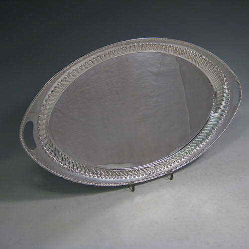 Antique Victorian sterling silver oval two-handled tea tray, having a plain ground, with swirl-fluted border and applied gadroon edge, all sitting on a flat base. This very handsome silver tray was made by Henry Holland of Sheffield in 1888. The dimensions of this fine hand-made silver tray are length 46 cms (18 inches), width 26.5 cms (10.5 inches), and it weighs approx. 891g (28.7 troy ounces).