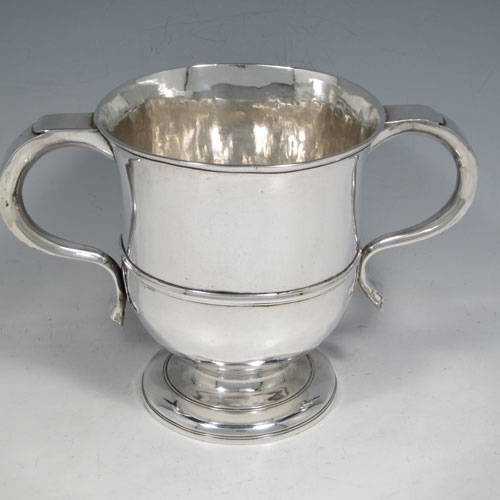 Antique Georgian George II Sterling silver trophy loving cup, having a plain round body with central reeded band, two scroll side-handles which are part-marked with a makers mark, and sitting on a pedestal foot. Made by Benjamin Blakely of London in 1738. The dimensions of this fine silver loving cup are height 14.5 cms (5.75 inches), spread across handles 23 cms (9 inches), and it weighs approx. 511g (16.5 troy ounces).