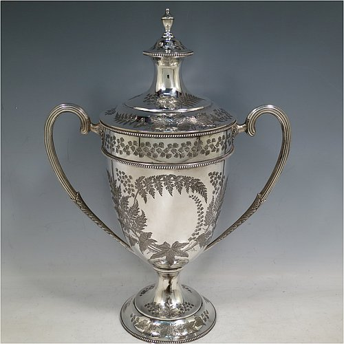 An Antique Victorian sterling silver trophy cup and cover, having a round hand-engraved body with fern, ivy, & gingko leaf decoration, a gold gilt interior and applied bead-edged borders, two cast and reeded scroll side-handles, an original cover with matching engraving and cast urn-shaped finial, and sitting on a pedestal foot. Made by John Newton Mappin (Mappin & Webb) of London in 1882. The dimensions of this fine hand-made antique silver trophy cup & cover are height 35 cms (13.5 inches), spread across arms 26 cms (10.25 inches), and it weighs approx. 857g (27.6 troy ounces). Please note that one side is engraved with an original presentation inscription for the Eastbourne Tennis Club in 1882.