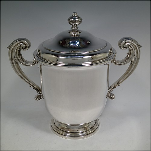 A very handsome and heavy Antique Victorian Sterling Silver trophy cup and cover, in a George II style, having a plain round body, two flying scroll side-handles with anthemion leaf thumb-pieces, a pull-off lid with cast finial, and all sitting on a stepped pedestal foot. Made by William Barnard of London in 1895. The dimensions of this fine hand-made antique silver trophy cup and cover are height 27 cms (10.5 inches), spread across arms 30.5 cms (12 inches), and it weighs approx. 1,787g (57.6 troy ounces).