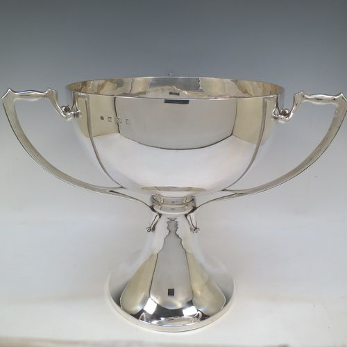 A very large and heavy Antique Edwardian Sterling Silver Art Nouveau three-handled trophy cup, having a plain round body, with three side-handles, and sitting on a plain pedestal foot. Made by Alexander Clarke & Co., of Birmingham in 1907. The dimensions of this fine hand-made large antique silver trophy cup are height 31 cms (12.25 inches), diameter of main body 27 cms (10.5 inches), and it weighs approx. 2,485g (80 troy ounces).