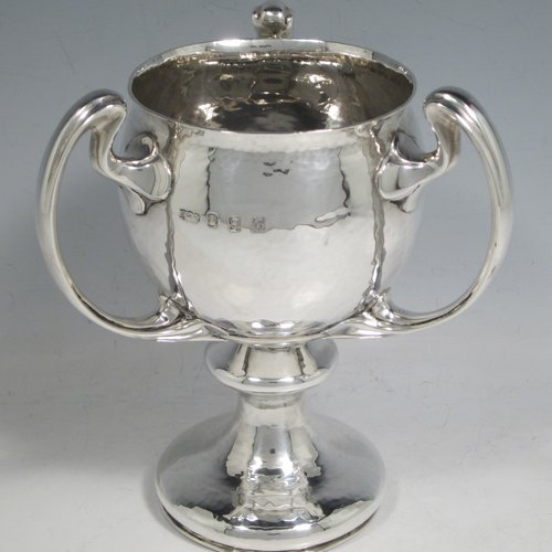 Antique Edwardian Irish sterling silver Art Nouveau style trophy loving cup, having a round body with hand-hammered decoration, three scroll handles with leaf-like ends, and sitting on a pedestal foot. Made by Elkington & Co., of Dublin in 1902. The dimensions of this fine hand-made silver trophy loving cup are height 17 cms (6.75 inches), width across handles 15 cms (6 inches), and it weighs approx. 558g (18 troy ounces).