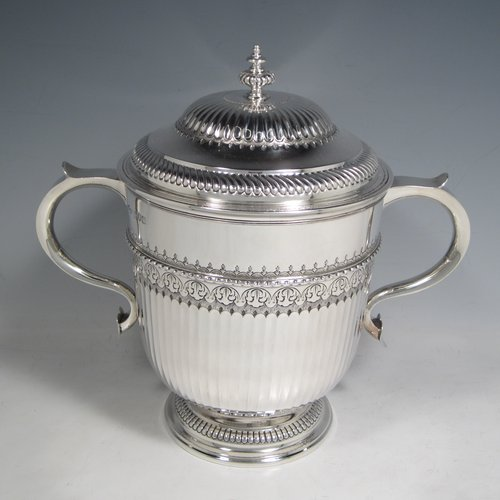 Antique Sterling silver trophy cup and cover, in a George II style, having a round body with hand-chased fluted and floral decoration, two scroll side-handles, a pull-off lid with cast finial, and sitting on a pedestal foot. Made Johnson, Walker & Tolehurst of London in 1912. The dimensions of this fine hand-made silver trophy cup and cover are height 24 cms (9.5 inches), spread across arms 26.5 cms (10.5 inches), and it weighs approx. 1,056g (34 troy ounces).