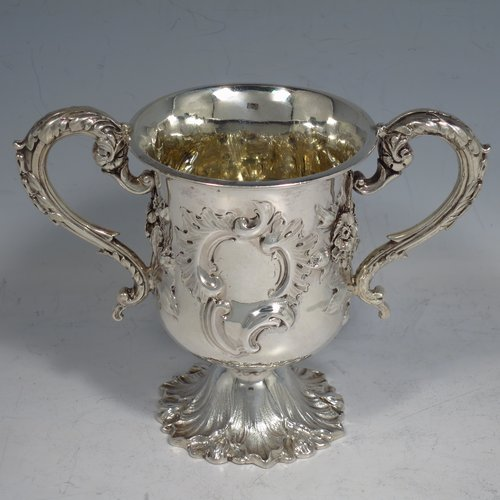 An Antique Victorian Sterling silver miniature trophy cup, in a Campana style, having a baluster body with a vacant cartouche on one side, and hand-chased floral decoration, with two cast floral scroll handles, a gold-gilt interior, and sitting on a spreading Acanthus leaf pedestal foot. Made by Charles Fox of London in 1839. The dimensions of this fine antique silver trophy cup are height 11 cms (4.25 inches), spread across handles 14 cms (5.5 inches), and it weighs approx. 185g (6 troy ounces).