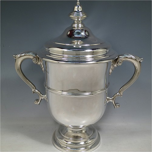 An Antique Edwardian Sterling Silver trophy cup and cover, in a George II style, having a plain round body, two scroll side-handles with anthemion leaf thumb-pieces, a central applied girdle band, a pull-off lid with finial, and all sitting on a stepped pedestal foot. Made by Martin & Hall of Sheffield in 1906. The dimensions of this fine hand-made antique silver trophy cup and cover are height 34 cms (13.5 inches), spread across arms 30.5 cms (12 inches), and it weighs approx. 1,497g (48 troy ounces).